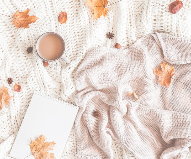 Off white sweater, coffee and brown leaves on a white blanket.