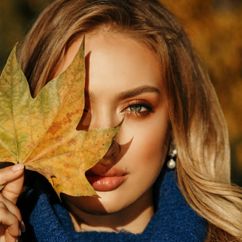 Woman holding a colorful leaf in front of her face while wearing Thanksgiving makeup.