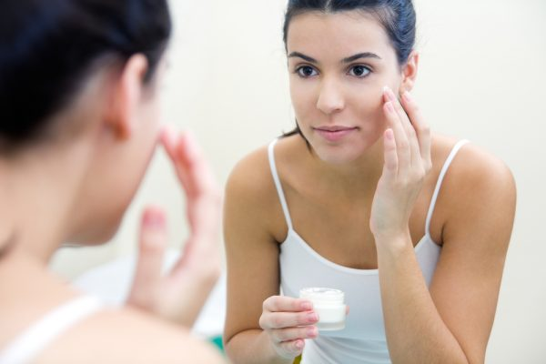 Woman applying moisturizer to her face for skin care.