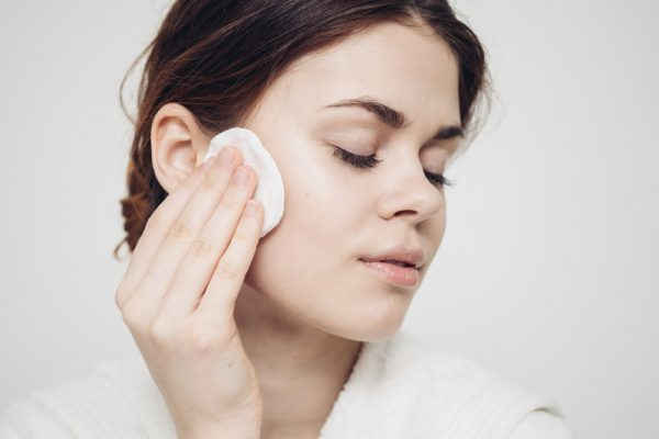 Woman applying toner to her face using cotton pad for skin care.