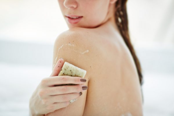 Woman rubbing a bar of soap on her skin during a luxe bath.