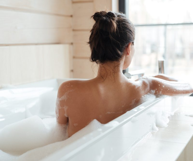 Woman taking a luxe bath.