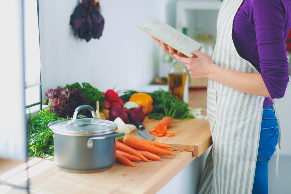 Woman reading clean eating cookbook in the kitchen.