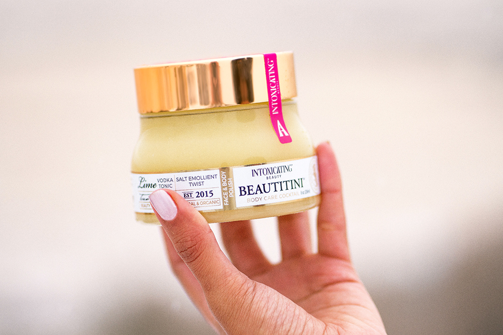 Intoxicating Beauty Beautitini Salt Emollient Twist, an alcohol-infused beauty product, being held into photo frame by a hand.
