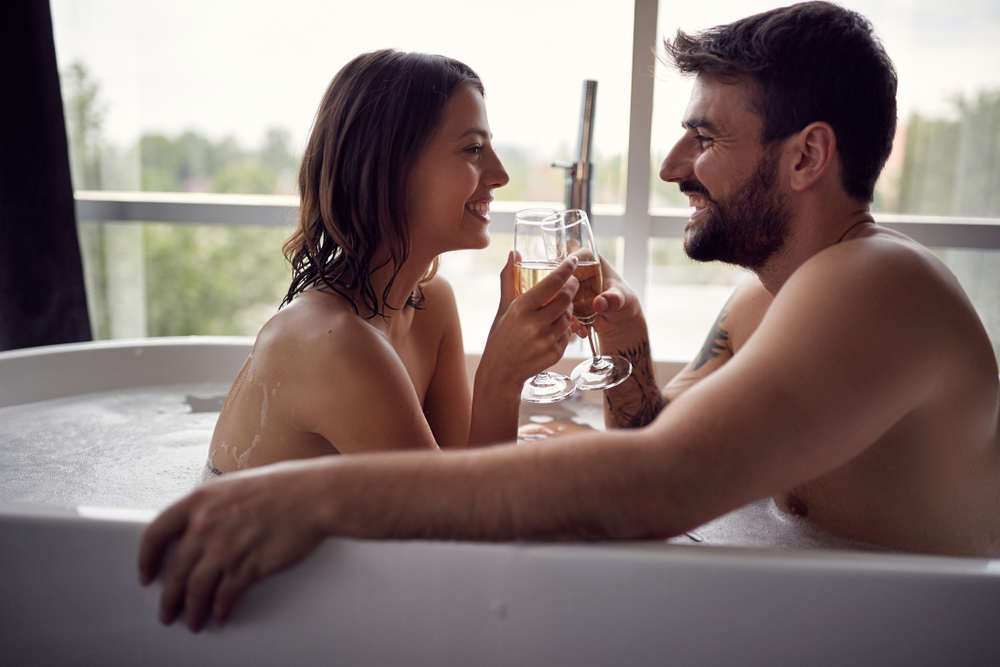 A couple during a bubble bath for two while enjoying a glass of champagne.