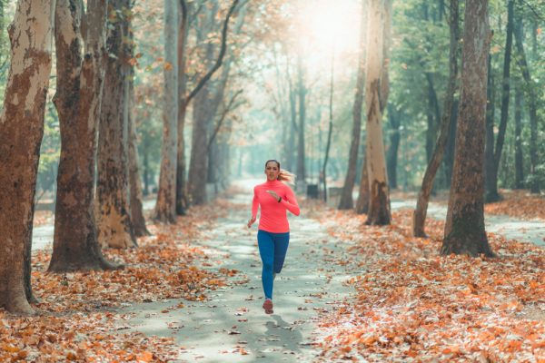 Woman running in the woods - enjoying outdoors is a method of practicing gratitude.