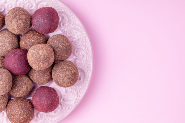Vegan deit friendly chocolate truffles on a pink background.