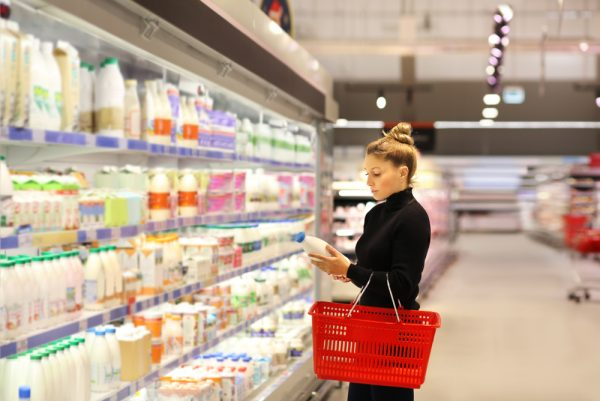 Woman choosing a vegan diet milk substitute while shopping at a grocery store.