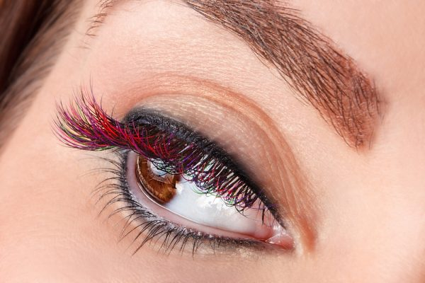Woman wearing red eyeliner - colored eyeliner is expected to be a makeup trend in 2020.