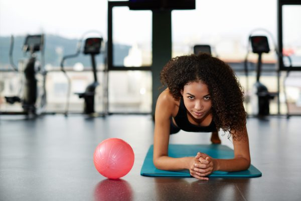 Woman with curly hair doing planks using gym essentials..