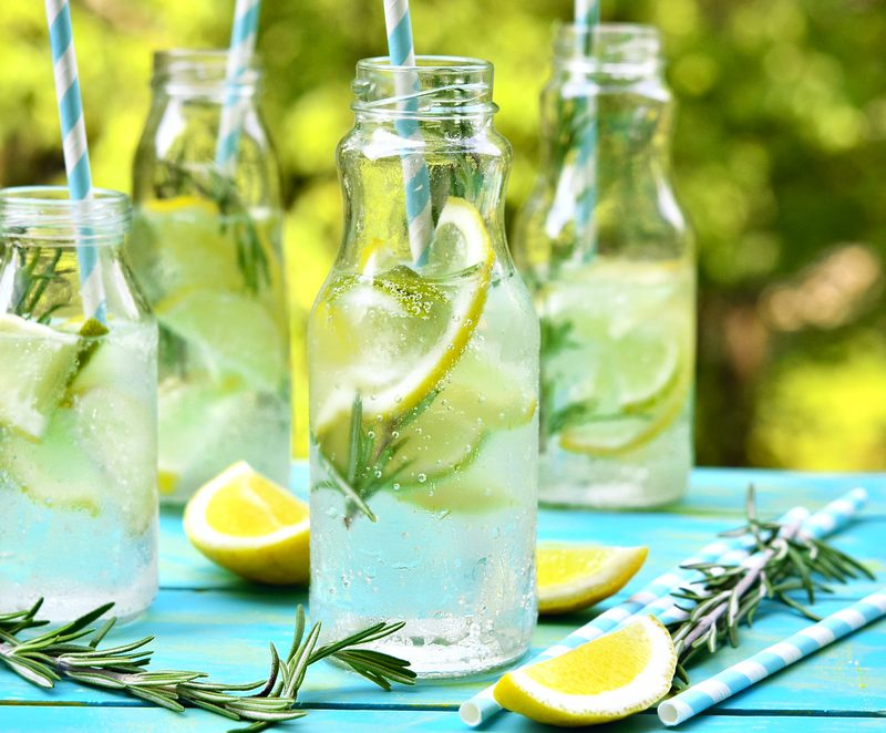 Selzter water in multiple jars sitting atop a blue table outdoors - try sparking water infused with hemp as alternative drink.