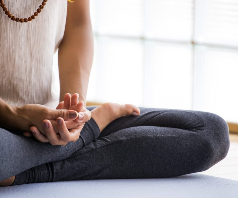 Woman doing yoga to practice mindfulness, one of 2020's wellness trends.