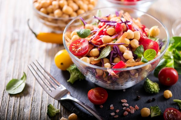 Bowl of vegetables, nuts, and fruits. Eating healthy is a continuing wellness trend in 2020.