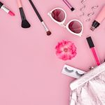 Makeup kit scattered across a pink background - pink is expeted to be a trending makeup color in 2020.