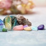Colorful crystals, used for holisitc wellness, lay on a flat blue surface.