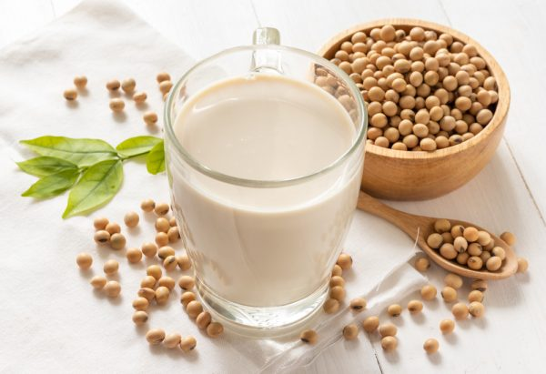Soymilk in glass and soy beans in a wooden bowl in the background - use soy milk as a milk alternative.