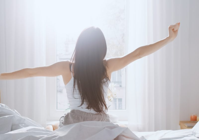 Woman getting out of bed in the morning - learn ways to switch up your morning routine.