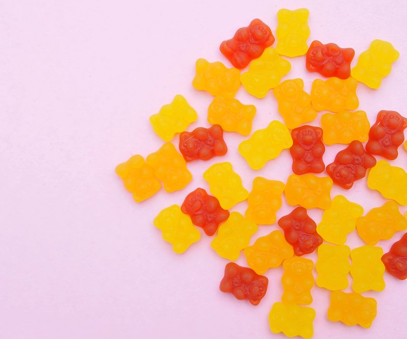 Vitamin gummies on a pink background - start your day with a vitamin supplements.