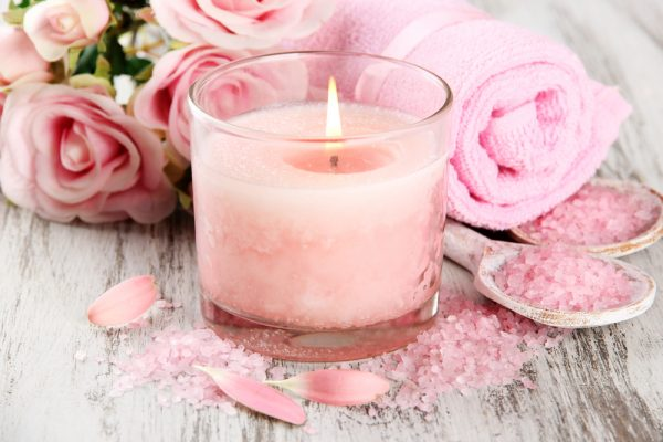 Pink candle burning surrounded by spa essential salts and towels - add candles to set your valentines day mood.