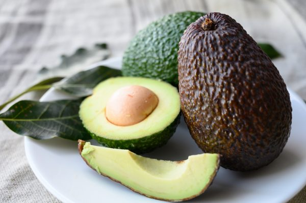 Avocados on a plate, both whole and sliced - add avocado to your beauty breakfast routine.