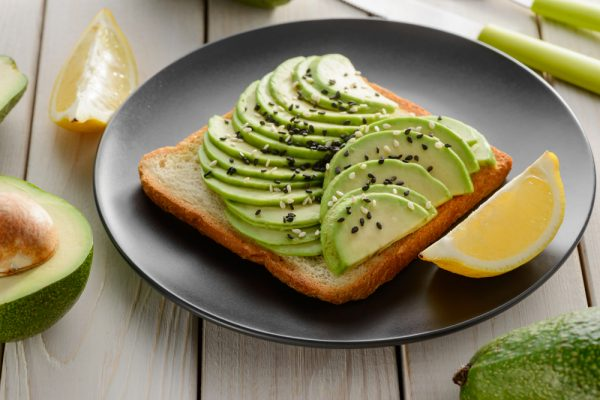 Avocado and toast with a side of lemon on a dark grey plate - try eating a plant based breakfast to spice up your morning routine.