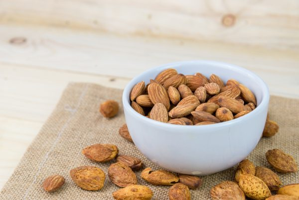 Almonds in a bowl on a brown cloth - use almond milk as a substitute for dairy.