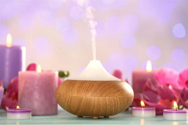 Aroma diffuser ,which can be used for holisitic wellness approaches, surrounded by lit pink and purple candles.