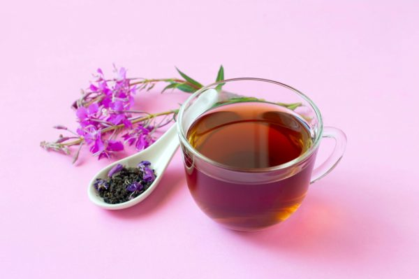 Tea in a small glass on a pink background surrounded by flowers and ingredients - consider using chai tea to reduce caffeine intake.
