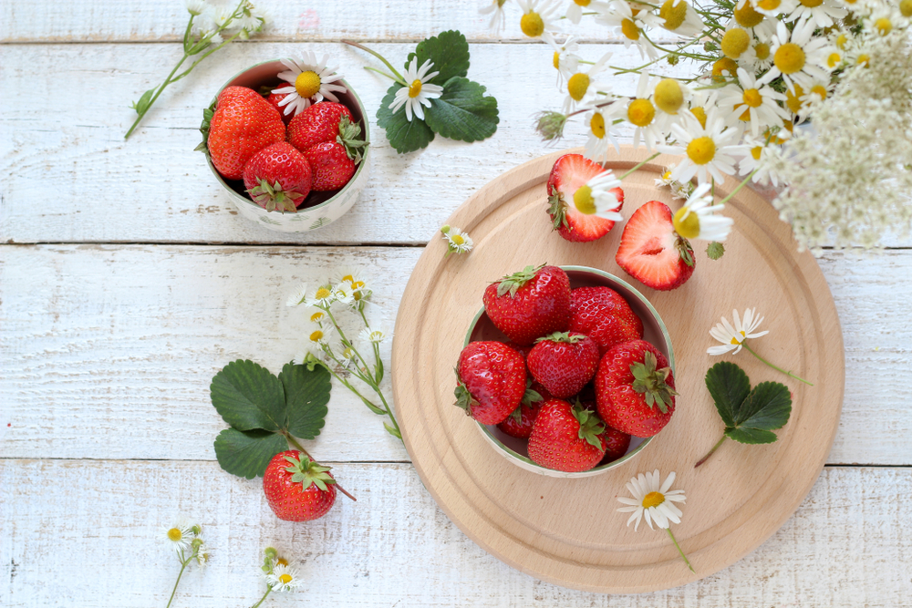 Strawberries, an antioxidant rich food, in a bowl on a wooden table surrounded by flowers.