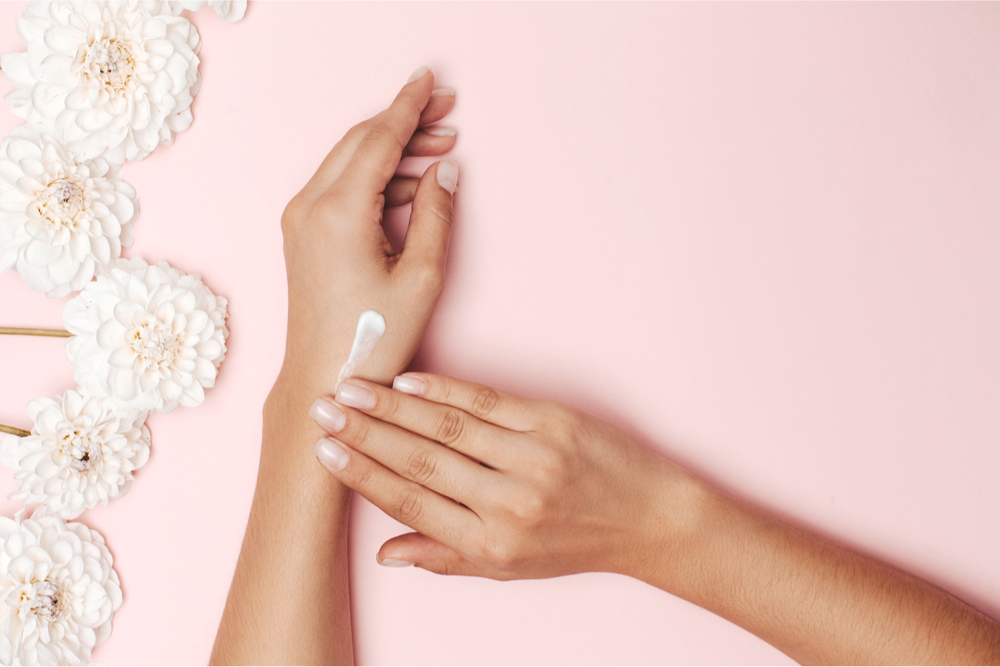 Woman massaging lotion into her hand on a pink background with white flowers.