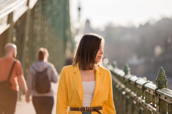 Woman in a bright yellow coat walking on a bridge - walking every day can help give you an energy boost.
