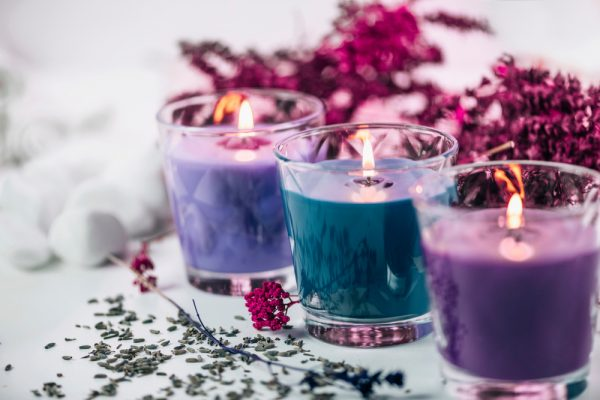 Lit scented candles of varying purple and blue colors - light some candles and use essential oils to calm moments of anxiety.