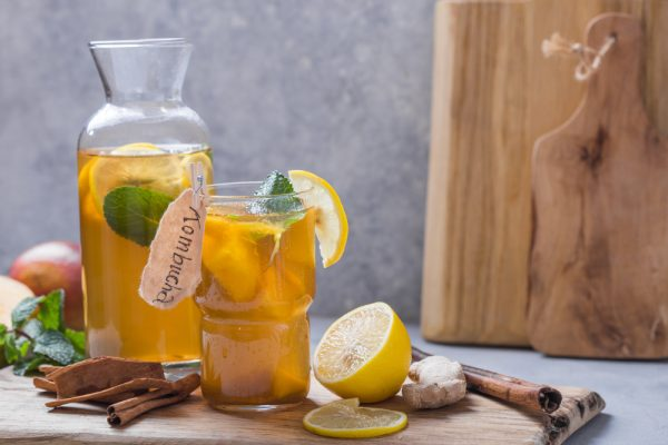 Kombucha in a glass container with ingredients on the side - use kombucha to dwindle your caffeine usage.
