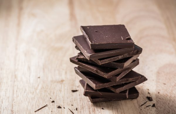 Dark chocolate, an antioxidant rich food, stacked on top of each other on a wooden background.