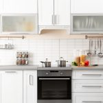 A modernized white kitchen with a black stove center piece - look to add our top essential items to your kitchen.