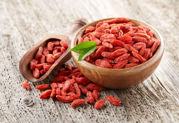 Goji berry, an antioxidant-rich food, in in a wooden bowl on a wooden background.