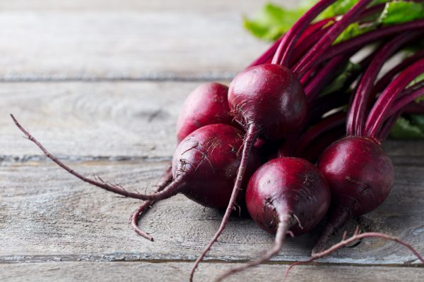Beets, a food rich in antioxidants, on a wood background.