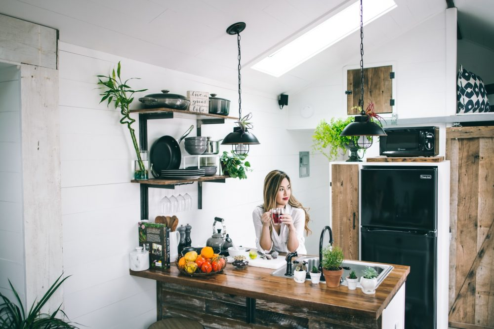 Woman sitting behind a kitchen table drinking tea and surrounded by plants.