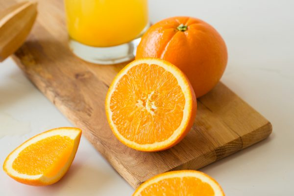 Oranges sit on top of a wood cutting board - oranges are delicious fruit for preventing grey hairs.