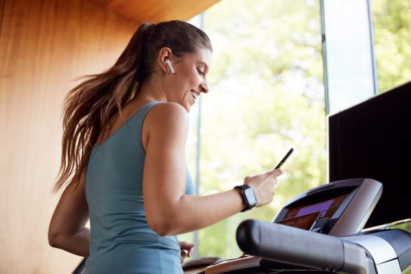Woman catching up with a friend on her phone while on the treadmill - have a friend motivate you while working out from home.