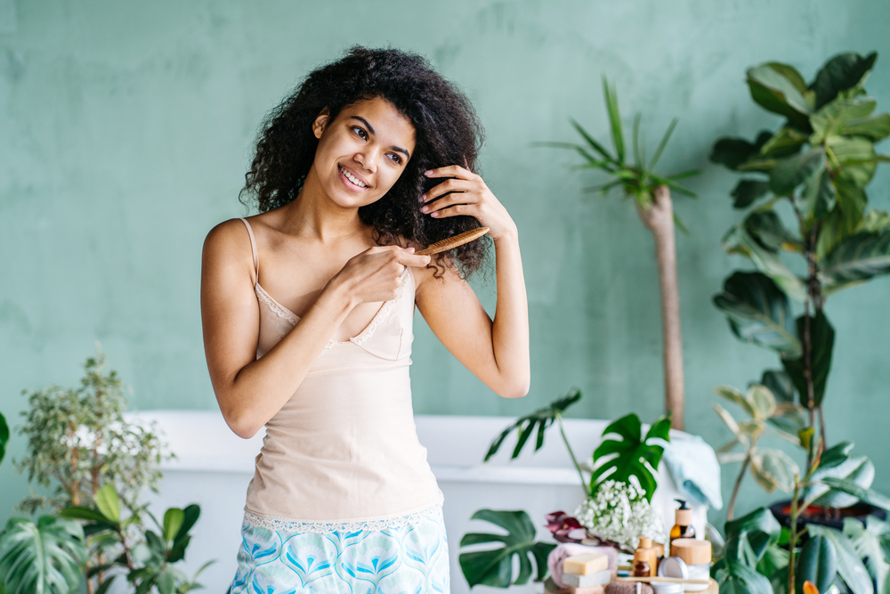 Woman in her pajamas combing through her hair at home. Change the way you style your hair during quarantine.