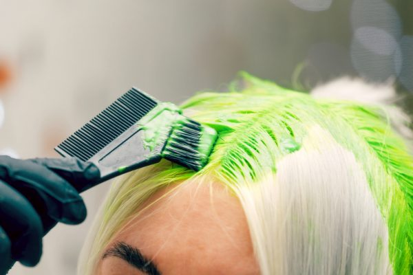 Self dyeing hair a light green color. Use temporary dyes to try out new hair colors.