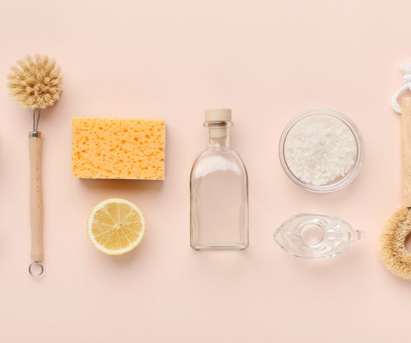 Cleaning tools on a pinkish background - go green with cleaning products; try using lemon, baking soda, and vinegar for example.