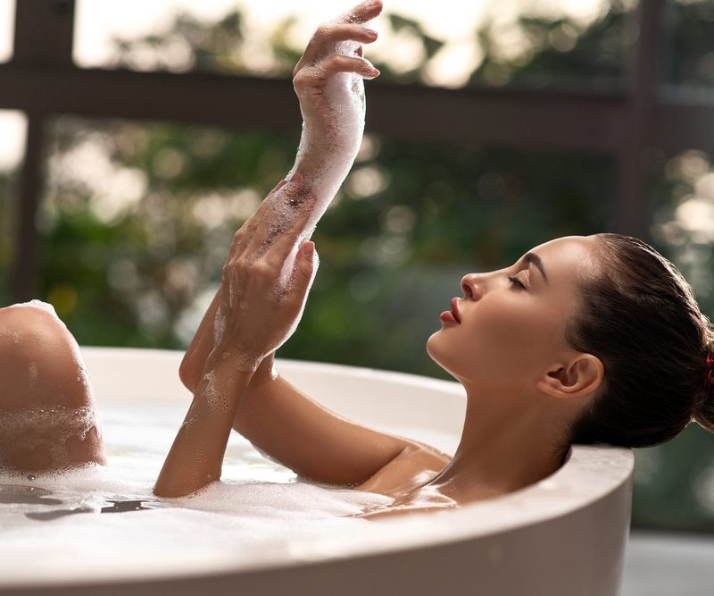 Woman in a bathtub rubbing soap on her skin - take advantage of quarantine time to keep up with your skin wellness.