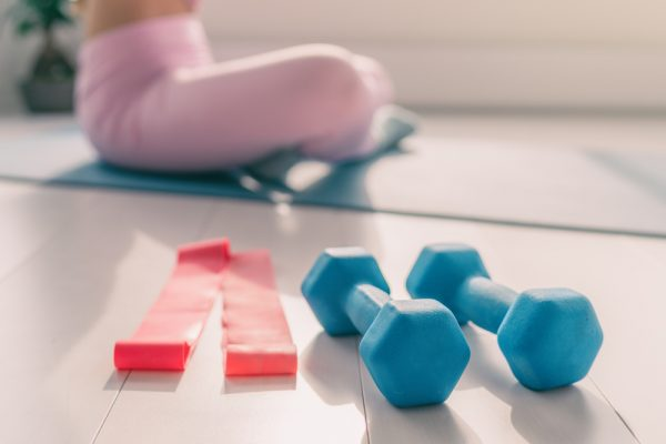 Resistance bands and weights in the foreground while a woman sits and exercises on a yoga mat in the background.
