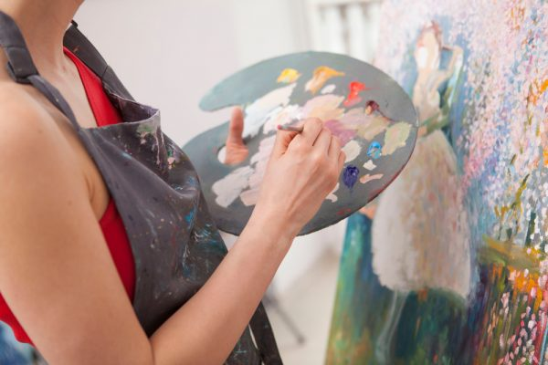 Woman with a paint tray and brush painting on a canvas - there's no better time than now to get creative and start getting into arts and crafts.