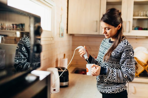 Woman in the kitchen frothing her milk for a coffee - have a virtual coffee date during stay at home orders.