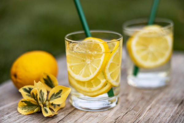 Two glasses of water with lemon and straw sit next to a flower and lemon on a table outside - avoid coffee when stressed as it can make anxiety increase.