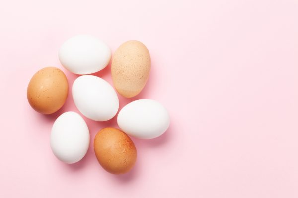 Multiple different types of eggs on top of a pink background - eggs are one type of food that can be eaten to prevent grey hairs.
