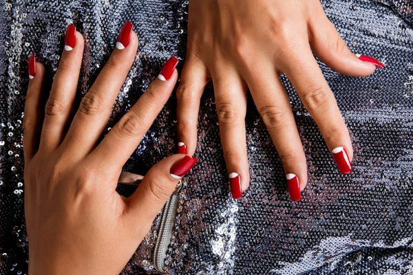 Woman with half moon manicure on top of silver sparkling dress - half moon nails leave out the bottom of the nail or uses a different color.